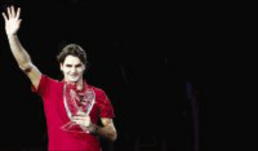 VIRTUOSO: Roger Federer of Switzerland poses with the trophy after winning the Masters Cup tennis tournament in Shanghai yesterday. Pic. Nir Elias. 18/11/07. © Reuters.