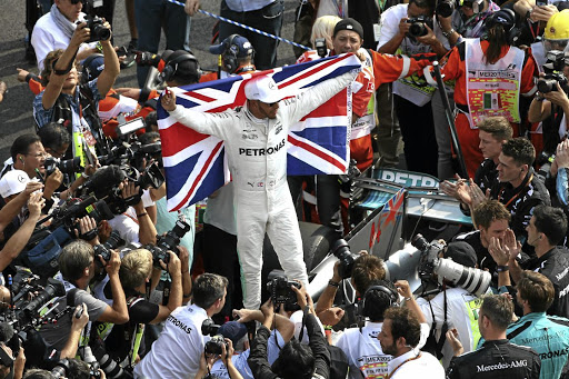 Lewis Hamilton is surrounded by photographers as he celebrates his fourth F1 title.