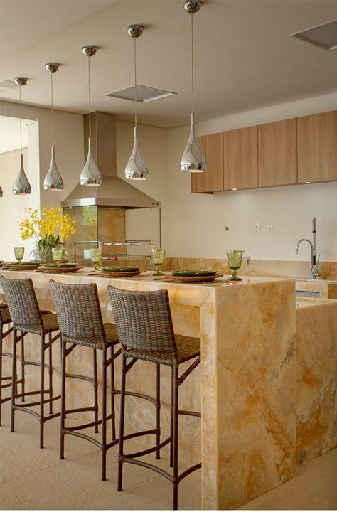 Área gourmet com churrasqueira de vidro, armários de madeira, bancada de pedra, cadeiras marrom e lâmpadas pendentes prateadas.