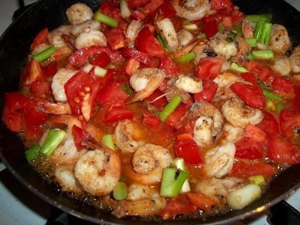 Add the Cajun seasoning, stir. Now, add salt and pepper to taste.  Add the tomatoes...