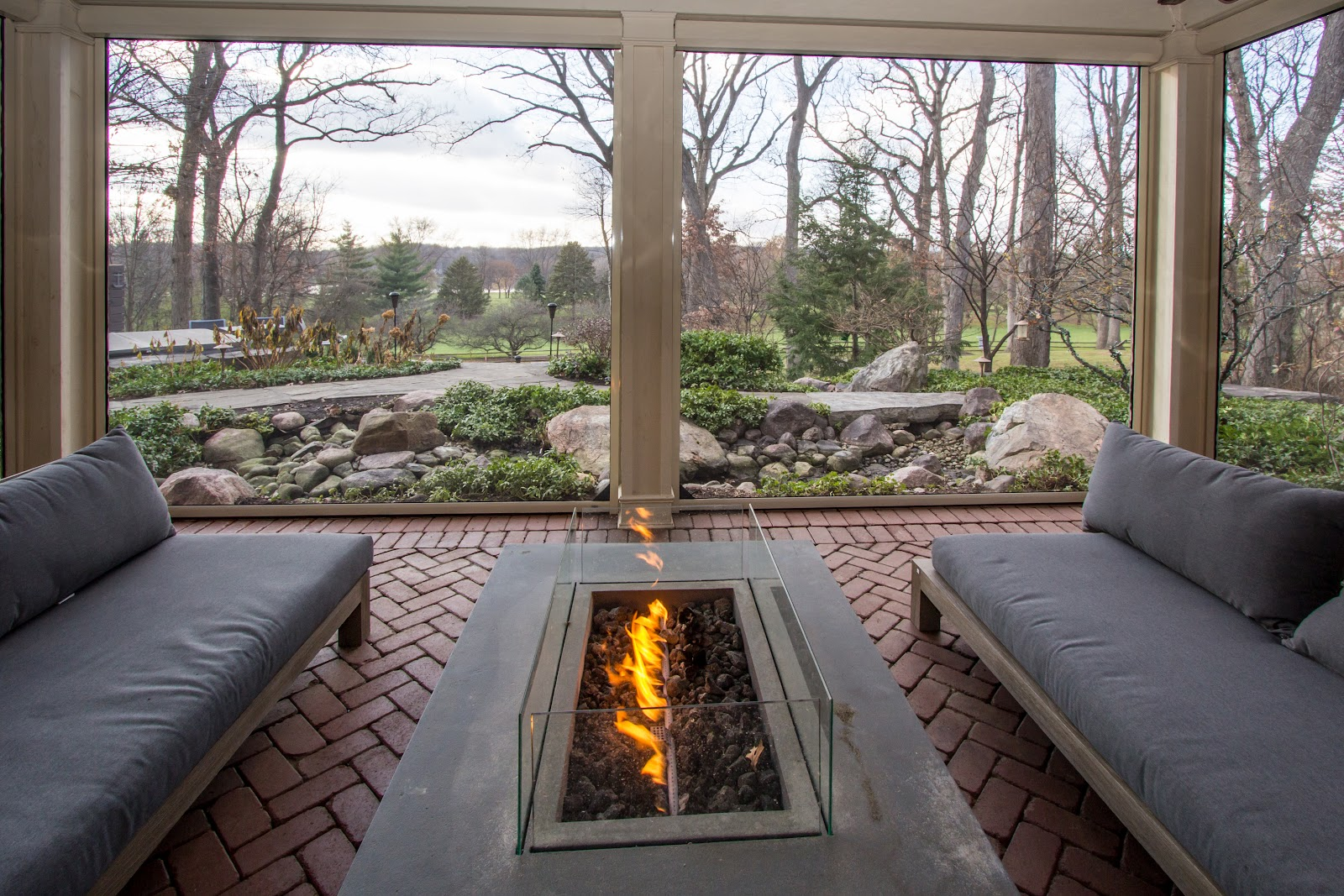 Herringbone brick-paved, indoor-outdoor patio with phantom screens and a fire table  overlooking a garden path