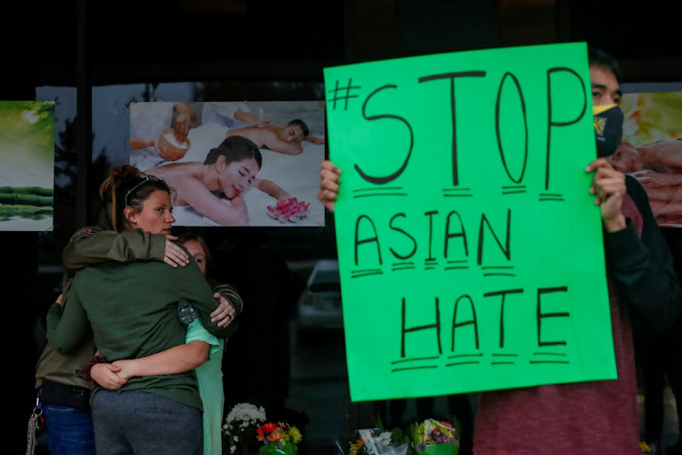 People grieve while Jesus Estrella, 21 holds a sign outside Young's Asian Massage following the deadly shootings in Acworth, Georgia, US March 17, 2021.