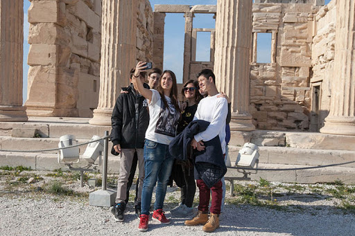 Millennial travelers pose for a selfie in front of the Erechtheion in Athens.
