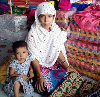 Sabina, a young woman wearing a white headscarf, kneels on the ground with a young child sitting next to her. They are surrounded by colorful fabrics.