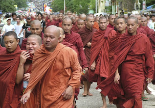 Photo: Buddhist monks, accompanied by civilians, march on a street in a protest against the military government in Yangon, Myanmar, Sunday, Sept. 23, 2007. About 20,000 Buddhist monks and citizens demonstrated against Myanmar's military junta in the country's largest city Sunday, with many shouting support for detained democracy leader Aung San Suu Kyi, witnesses said (AP Photo)