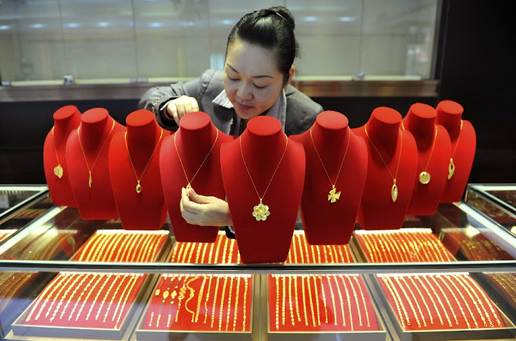 A shop assistant arranges gold accessories at a gold store in Lin'an, Zhejiang province, China. Picture: REUTERS