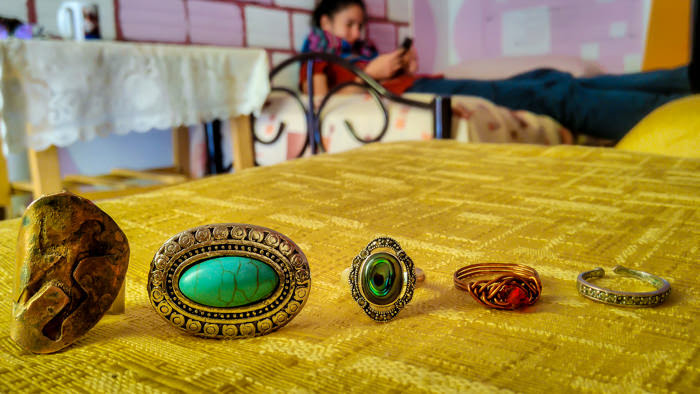 a collection of turquoise, abalone, copper, bronze, and silver rings on display.