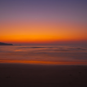 Depicts one of those amazingly beautiful moments when the sun sets and moon rises. The gentle lashing of the waves set against the varied hues of the setting sun gives this click a hauntingly ethereal beauty. The moon found high in the sky as a silvery blob adds to the mystique of the expanse.   by Raghu Lakshminaarayanan - Landscapes Waterscapes
