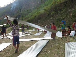 Photo: Afectados por el terremoto recogiendo láminas de metal para sus cabañas en la aldea de Khalte, distrito de Dhading.