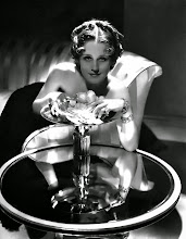 Photo: Hollywood in the 1930's was still fascinated by Art Deco. That style heightens the aestheticism of the glamour portrait genre.  In this case, photographer George Hurrell photographs MGM leading lady Norma Shearer using extravagant lighting, decor, and jewelry. The circular patterns of the table and the couch's arm add a strong visual pattern.  Hurrell boldly uses a much dimmer 'key light' on the actress's face and 'exposes' the use of a light on the hair to bring out its sheen (and to separate the figure from the background in black-and-white photography).  The reflected light from the table and the flower petals softens the light on the face.
