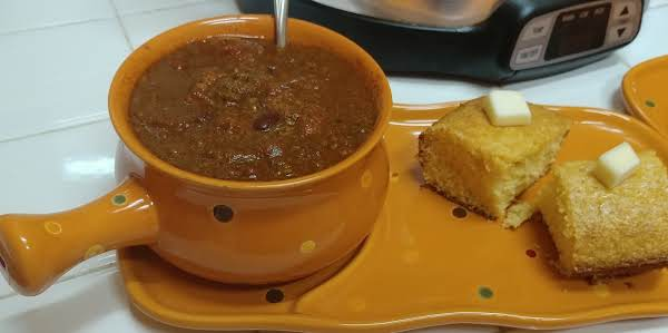 A Hot Cup Of Chili With Cornbread And Butter.