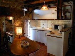 Photo: Cuisine équipée : ustensiles de cuisine, cafetière, 1 frigo, 1 four électrique, 1 micro-onde, 1 plaque de cuisson gaz 4 feux. A l'avant : une table de travail en châtaignier.