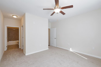 Bedroom with light carpet, ceiling fan, and attached bathroom
