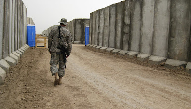 Photo: A Red Bull Soldier walks along the T walls that protect his Containerized Housing Unit (CHU) in Basra, Iraq. The 34th Red Bull Infantry Division is currently deployed to Basra, Iraq in support of Operation Iraqi Freedom. Photo by Staff Sgt. Jamieson Pond of TheRedBulls.org.