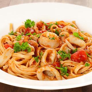 Squid In Marinara Sauce Over Linguine.