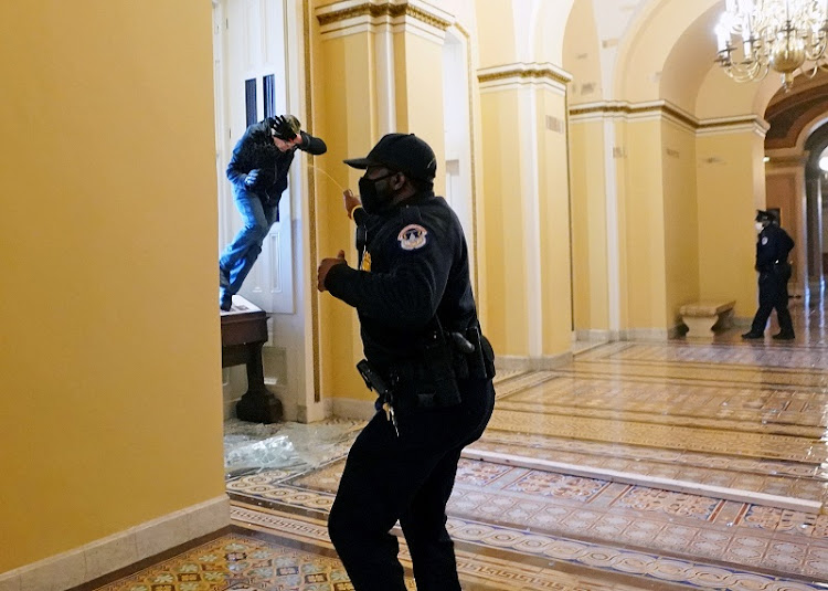 A U.S. Capitol police officer shoots pepper spray at a protestor attempting to enter the Capitol building during a joint session of Congress to certify the 2020 election results on Capitol Hill in Washington, U.S., January 6 2021.