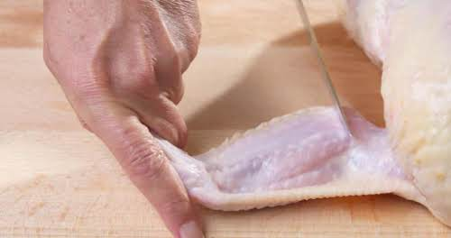 Step 3. Separate the wings from the chicken by slicing through the...