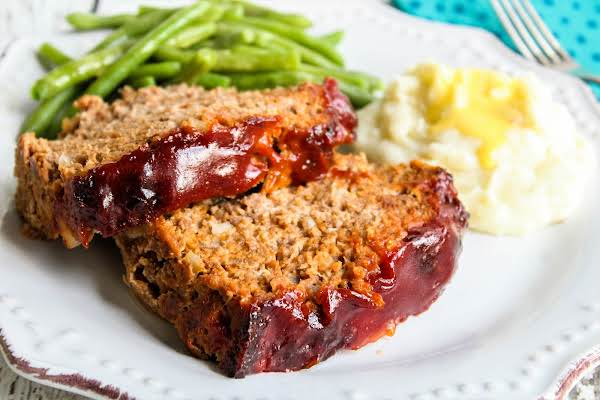 Two Slices Of Brown Sugar Glazed Meatloaf On A Plate.