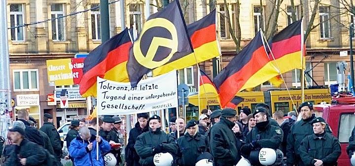 Demo mit Polizeischutz. Fahnen in Schwarz-Rot-Gold, dazwischen die der Identitären: Gelber Winkel im Kreis auf schwarzem Tuch.