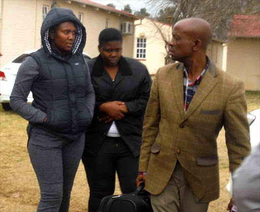 IN HOT WATER: Nyameka Qongqo, left, and her sister Thumeka, during their arrest in Queenstown Picture: ABONGILE MGAQELWA