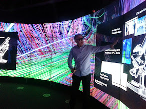 Photo: Professor Paul Bonnington, Director of the Monash e-Research Centre, demonstrates how the CAVE2(TM) facility works and what kind of data can be displayed.  Imagery courtesy of UIC EVL, CALIT2 UCSD, Australian Synchrotron, KAUST, and Monash University