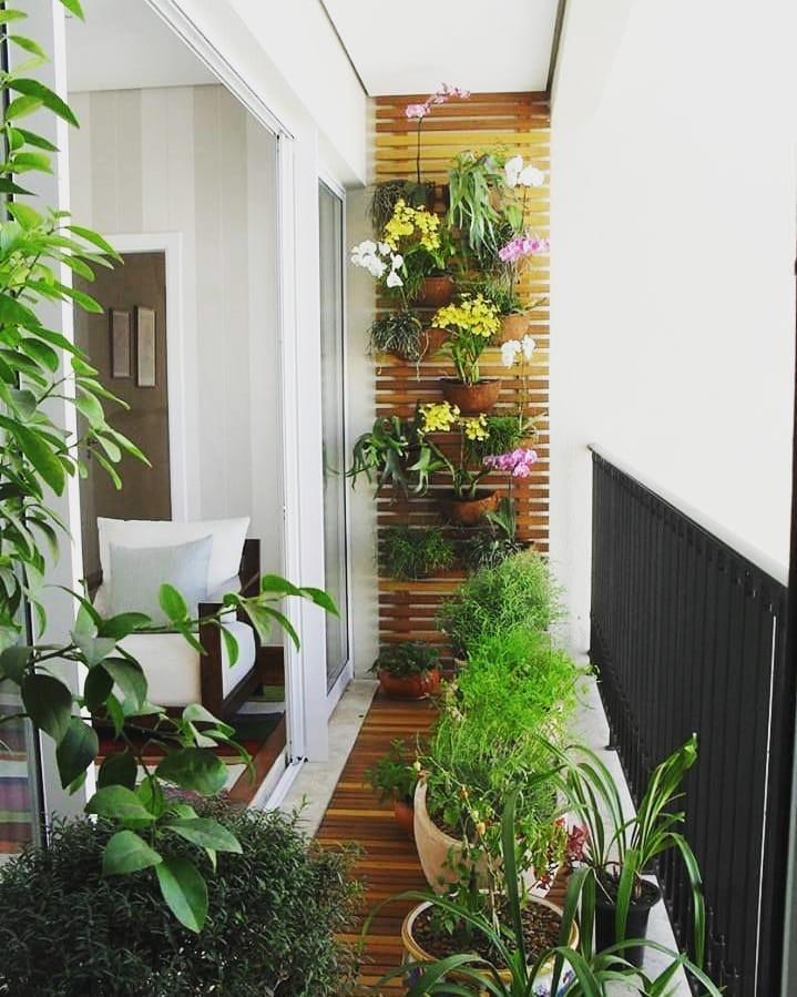 Varanda pequena com um lindo painel de madeira formando um jardim vertical e vasos de plantas espelhados pelo chão.