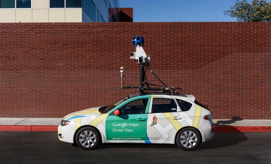 Street View-Auto für Google Maps mit Luftsensor auf dem Dach, geparkt vor einem roten Backsteingebäude