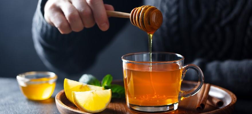 Mężczyzna słodzący herbatę miodem