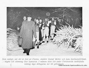 """Photo: Disponent Nils Eriksson - Flenmon - på Flenmo gård i Mellösa älskade den sörmländska folkmusiken och dess spelmän. Han bjöd spelmännen på storstilade fester och bilden är nog från 1946 då ett gille på Flenmo föregick årsmötet i Flen. I spetsen gär """"Förkörarn"""" Erik Robert Jansson, som var en viktig man i Mellösa. Bild ur skriften Mellösa på Barnens dag 1950."""