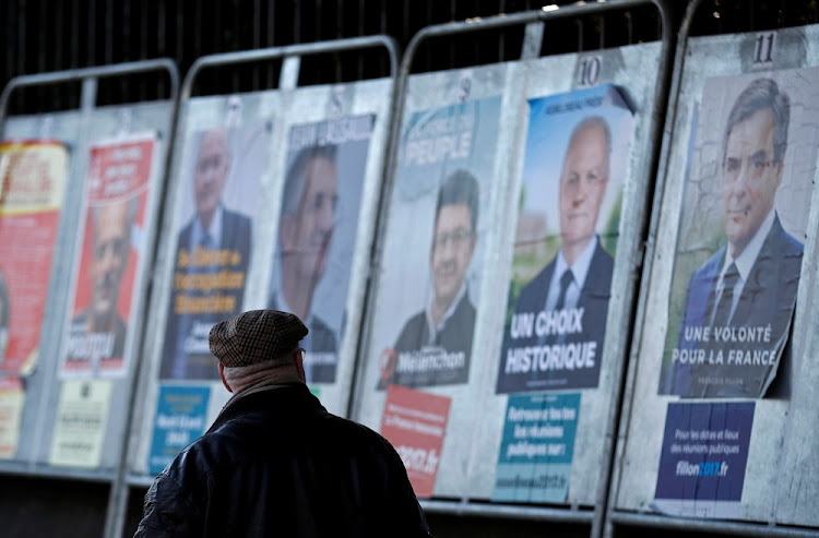 A man looks at campaign posters of the 11 candidates who are running in the 2017 French presidential election in Enghien-les-Bains, near Paris, France, on Wednesday.     Picture: REUTERS