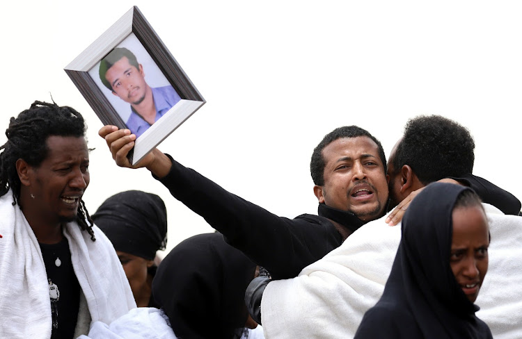 A relative holds a portrait as he mourns at the scene of the Ethiopian Airlines Flight ET 302 plane crash, near the town Bishoftu, near Addis Ababa, Ethiopia March 14, 2019.