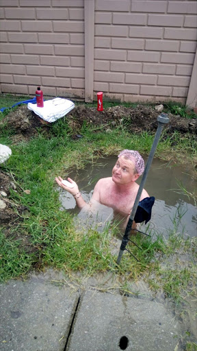 Democratic Alliance councillor Tim Denny bathes in a sinkhole a burst pipe created in his backyard in Secunda, Mpumalanga.
