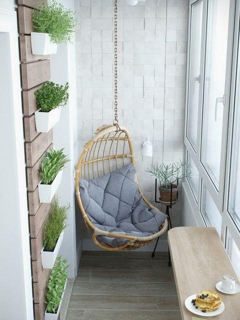 Varanda com cadeira de balanço pendente, painel de madeira na parede com vasinhos de plantas, piso amadeirado cinza e bancada de madeira.
