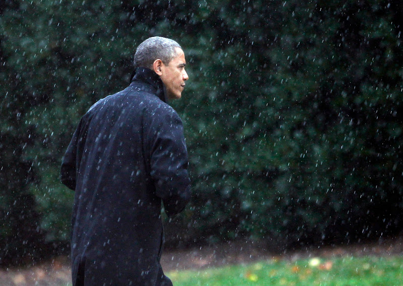 Photo: U.S. President Barack Obama walks through the rain to the Oval Office of the White House upon his return to Washington.