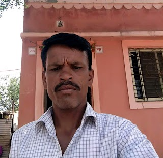 A photo of Bharat, a father with short black hair and a mustache, standing outside in front of an earth-toned building.