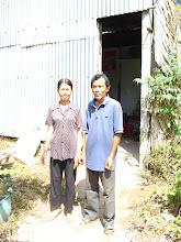 Photo: Minh và phu nhân đứng trước căn nhà tạm bợ trên miếng đất sắp giải tỏa