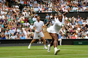 Serena Williams of the United States, playing partner of Andy Murray of Great Britain plays a backhand in their Mixed Doubles second round match against Fabrice Martin of France and Raquel Atawo of the United States during Day Eight of The Championships - Wimbledon 2019 at All England Lawn Tennis and Croquet Club on July 09, 2019 in London, England.