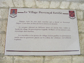 "Photo: The fortified Provençal village. Séguret comes from the Latin word ""securitas"" which gave in Provençal ""Ségur."" This is thus a place where one can be in safety. The defensive rampart of the 14th century is still quite visible in front of the village. In Provençal it is called ""le Barri"" and one finds again this etymology in ""barrière."" The defensive walls and gates of the village kept a permanent guard, while the watchmen on the castle hill surveyed the plain."