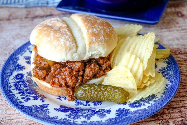 Sloppy Joes On A Roll With Chips And A Pickle.