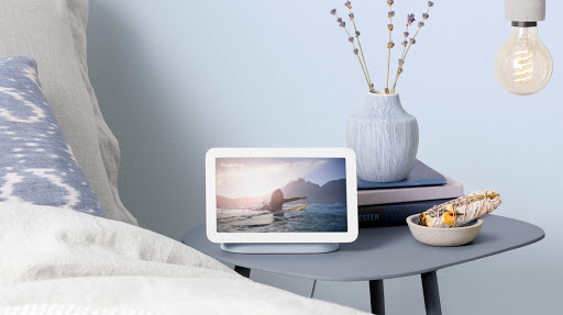 Nest Hub is located on a wooden table displaying pastel colors on screen and surrounded by pottery and tools.