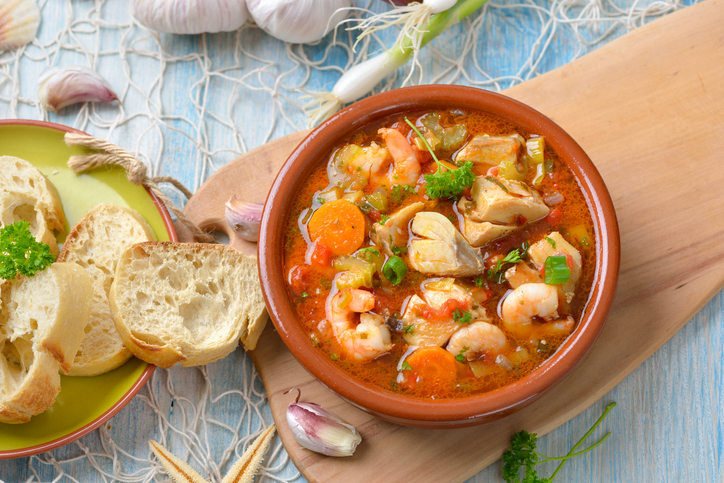 A bowl of bouillabaisse served with bread