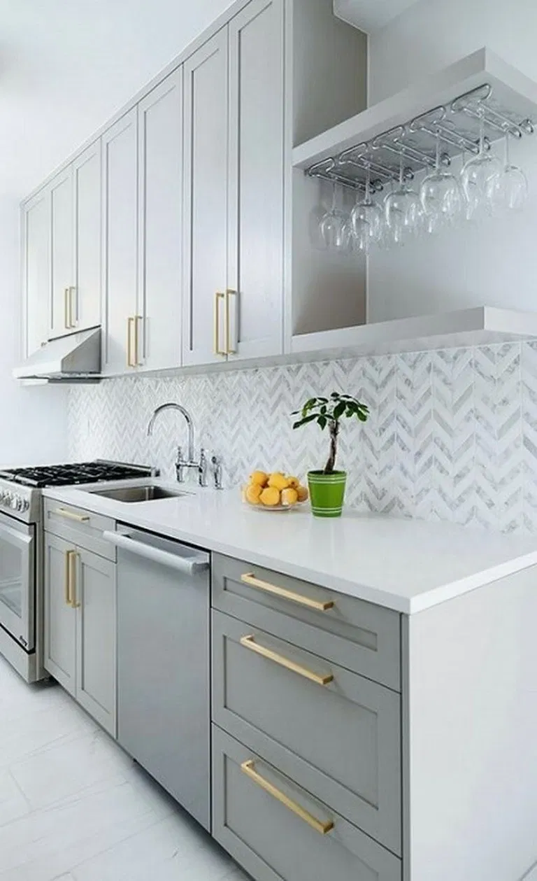 modern kitchen with grey shaker cabinets, steel appliances and brass cabinet pulls