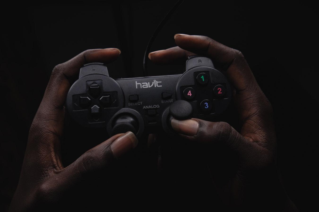 一雙手握著黑色遊戲握柄。