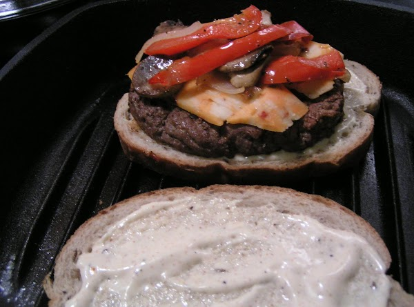 Next, place hambuger steak on bread, a layer of cheese, a layer of veggies...