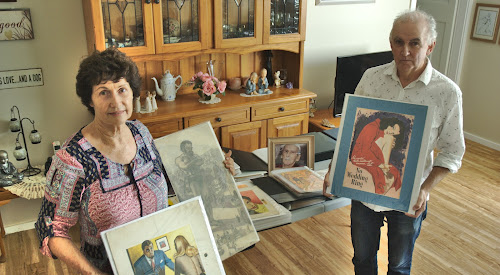 Meg Madden, the widow of Peter Chapman (whose photo is in the background), and Macquarie University Associate Professor Peter Doyle with some of the varied works that will be featured in an exhibition of Mr Chapman's work  in Sydney.