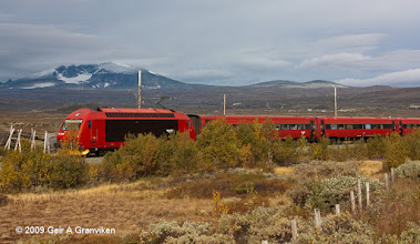 Photo: The NSB Dovre Express passing the highest point of the Dovre line, with Snøhetta in the background (El18 electr. locomotive)