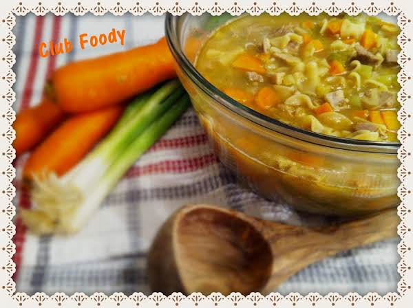 Turkey Noodle Soup In A Large Glass Bowl Sitting On A Dish Towel With A Wood Ladle, A Bunch Of Green Onions And Carrots.