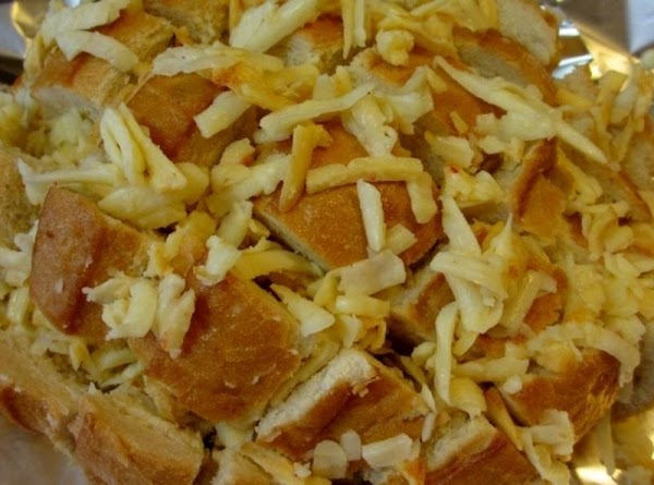 Stuff every slit in the bread with the cheese. Any left over cheese, sprinkle...