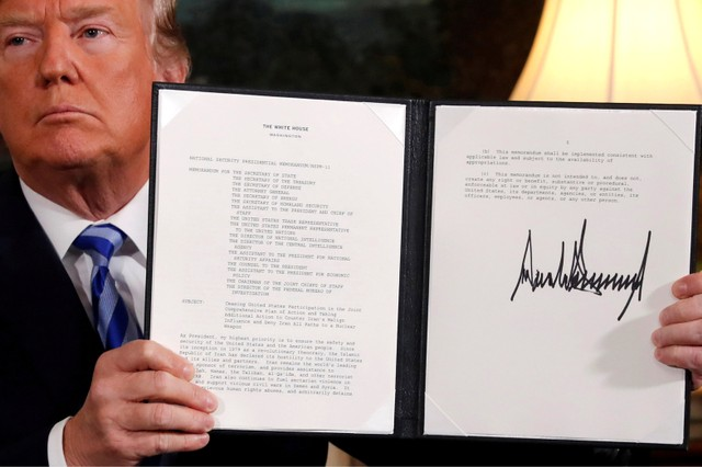 US President Donald Trump holds up a proclamation declaring his intention to withdraw from the JCPOA Iran nuclear agreement after signing it in the Diplomatic Room at the White House in Washington, US May 8, 2018.