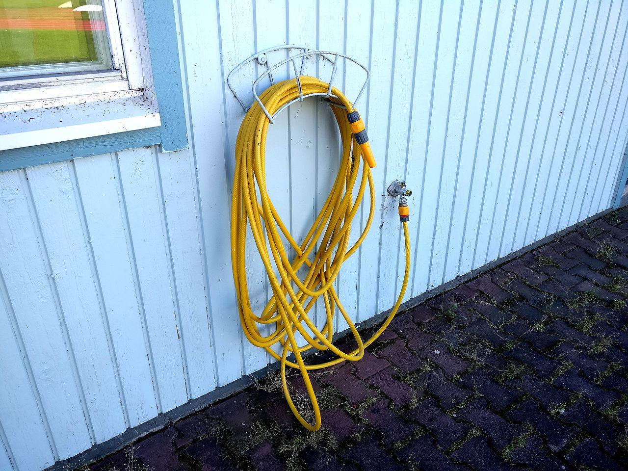 A garden hose hanging on a metal hanger
